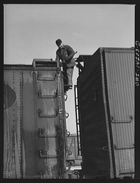 Rear brakeman inspects train and releases all handbrakes before train pulls out of Proviso yard for Clinton, Iowa (on a trip aboard a Chicago and Northwestern Railroad (C&NWRR) freight train)