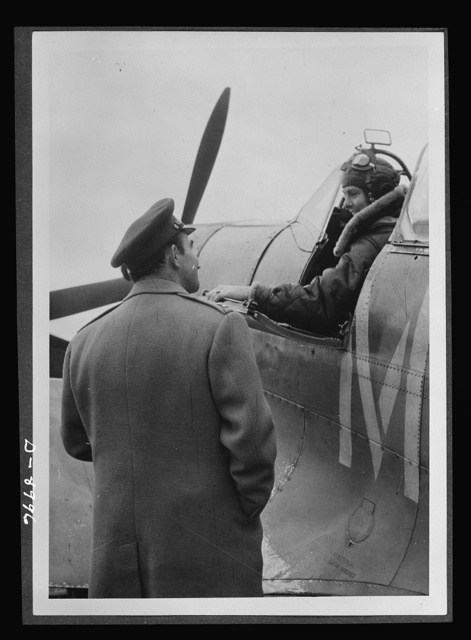 Reciprocal aid. Two gentlemen from Ohio who pilot Spitfire planes in Britain. Lieutenant E.S. Schofield of Belleville, wearing a British flying kit, and R.F. Sargent of Youngstown, wearing a British Irvin jacket, give evidence of the cooperation between British and American air forces. Important equipment and supplies including airdromes, barracks and ammunition, are provided American fighting forces under the British Reciprocal Aid Program