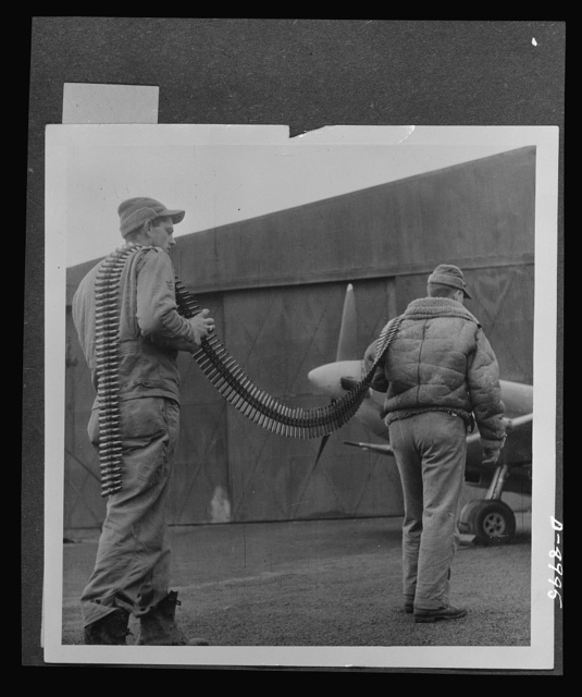 Reciprocal aid. Two sergeants from Texas, Sergeant A. Baker and Technical Sergeant Roy Hill, carry a string of British bullets over their shoulders to a British Spitfire. American and British air forces work side by side in the European theatre, with British furnishing important supplies and equipment under the Reciprocal Aid Program