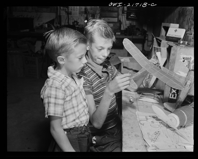 Rochester, New York. Earl and Howard Babcock looking over one of the model airplanes which Howard built