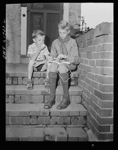 Rochester, New York. Earl Babcock watching while Howard, his brother, in his Boy Scout uniform, practices tying knots