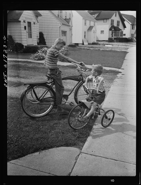 Rochester, New York. Howard and Earl Babcock playing in front of their house with their cycles