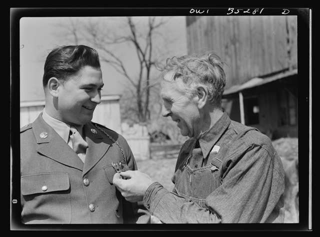 Rockville (vicinity), Maryland. Private Harvey Horton, visiting the N.C. Stiles dairy farm while on furlough from Fort Belvoir, Virginia with farmer Stiles who is questioning him about his medals