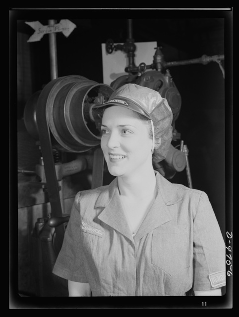 Safe clothes for women war workers. Her hair tucked away under a safety cap, war worker Eunice Kimball stands beside whirling machine wheels with no wisp of hair exposed. She's completely protected from the danger of entanglement in moving machine parts. Bendix Aviation Plant, Brooklyn, New York