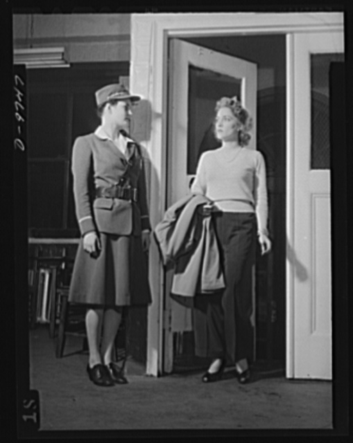 Safe clothes for women workers. Illustrating what the well-dressed women in search of a war job should NOT wear, pretty Eunice Kimball, Bendix Aviation worker, pauses at the entrance to the plant employment office where potential workers are interviewed. Though clothes may not make the woman, they ARE an indication of qualifications for a job, and Eunice's sweater, high-heeled and open-toed slippers, jewelry and loose hair-do are not improving her chances of employment. To contrast the inappropriateness of her costume, note trimly-dressed Alice Tripp, Bendix guard.  Bendix Aviation Plant, Brooklyn, New York
