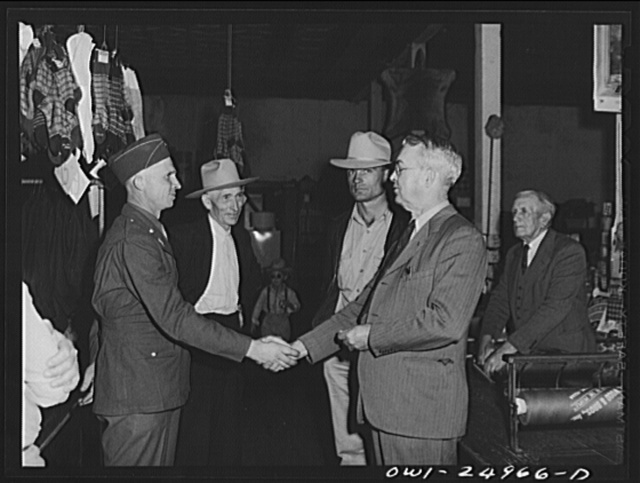 San Augustine, Texas. A.J. Wood, owner of the clothing store, shaking hands with a soldier home on furlough