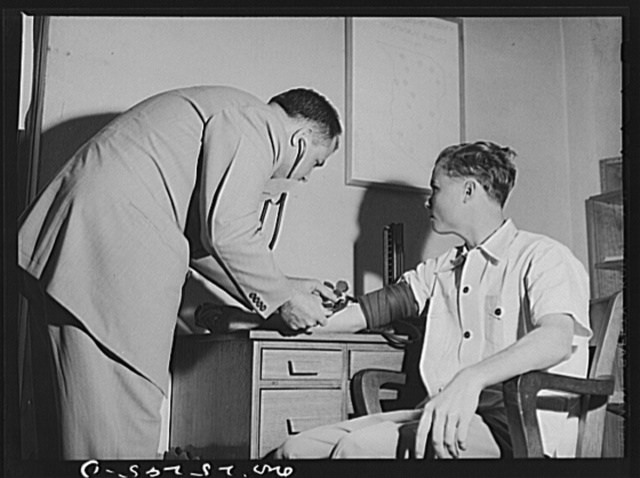 San Augustine, Texas. Dr. Jones taking the blood pressure of the grocer's boy who has just turned eighteen and is about the be inducted into the Army