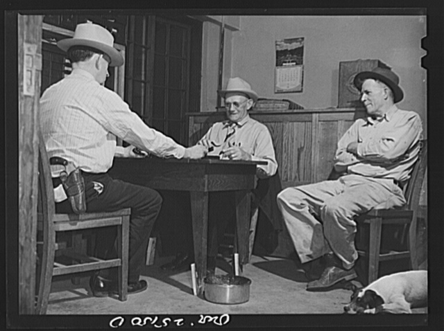 San Augustine, Texas. Lud Behnholder, filling station operator, watching night marshall Jeff Davis and the Justice of the Peace H.L. Armstrong in a domino game