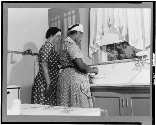 San Augustine, Texas. Mrs. Thomas, the wife of a wholesale grocer, in her kitchen with her maid