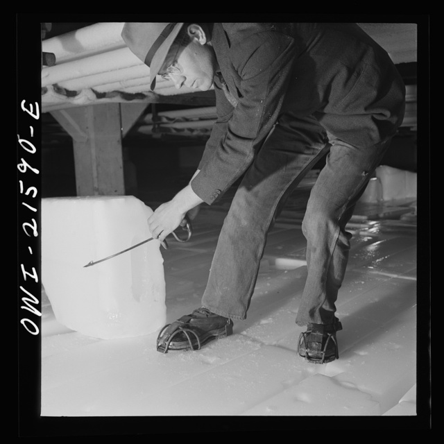San Bernardino, California. Workman handling ice in the storage room at the ice plant