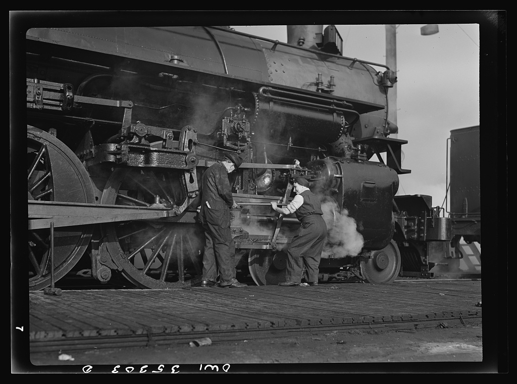 San Francisco, California. A woman railroad worker learning how to grase an engine wheel