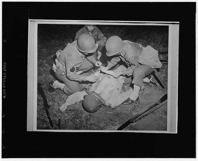 San Francisco, California. First aid demonstration at the Presidio of the proper method of treating an abdominal wound by keeping it moist until the patient can be removed to a field hospital, perhaps by improvising a stretcher by army blankets and rifles