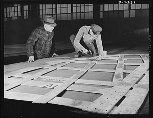 """Shipbuilding. """"Liberty"""" ships. This worker is laying out steel plates from wood templates, or patterns. The patterns indicate rivet hole locations and other necessary information. All parts are prefabricated in this Eastern plant which used to turn out freight cars. Completed sections are carried six miles to the ways on flat cars. Bethlehem-Fairfield Shipyards Inc., Baltimore, Maryland"""