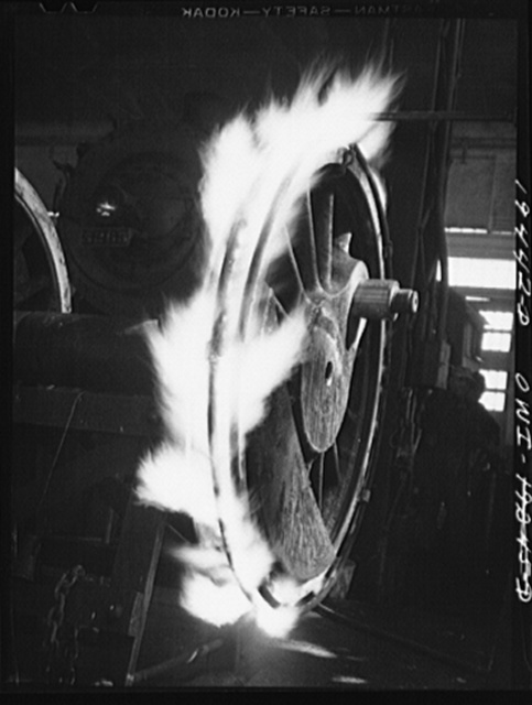 Shopton, near Fort Madison, Iowa. Retiring a locomotive driver wheel in the Atchison, Topeka and Santa Fe Railway locomotive shops. The tire is heated until it expands sufficiently to be slipped onto the wheel. Contraction on cooling will hold it firmly in place