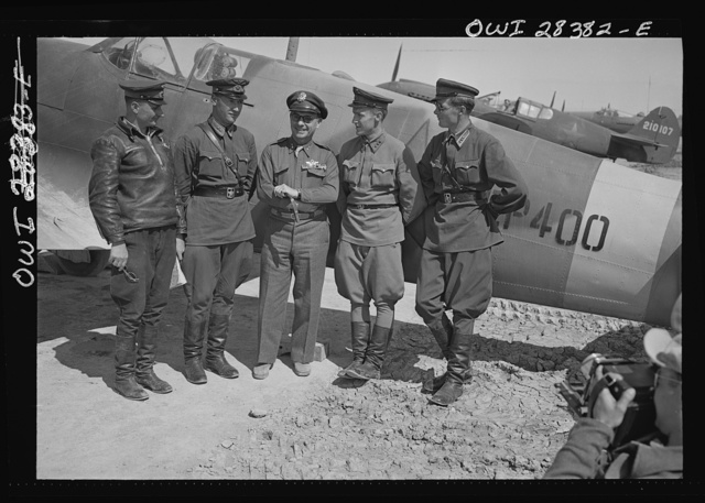 Somewhere in Iran. Major General Lewis Brererton in the center, the Commander of the United States Army force in the Middle East, with a group of Russian officers standing before an American warplane delivered to the Russians. A United States warplane is being tested in the background and bears the red star insignia of Russia, which is made by filling in the white star of the United States with red paint