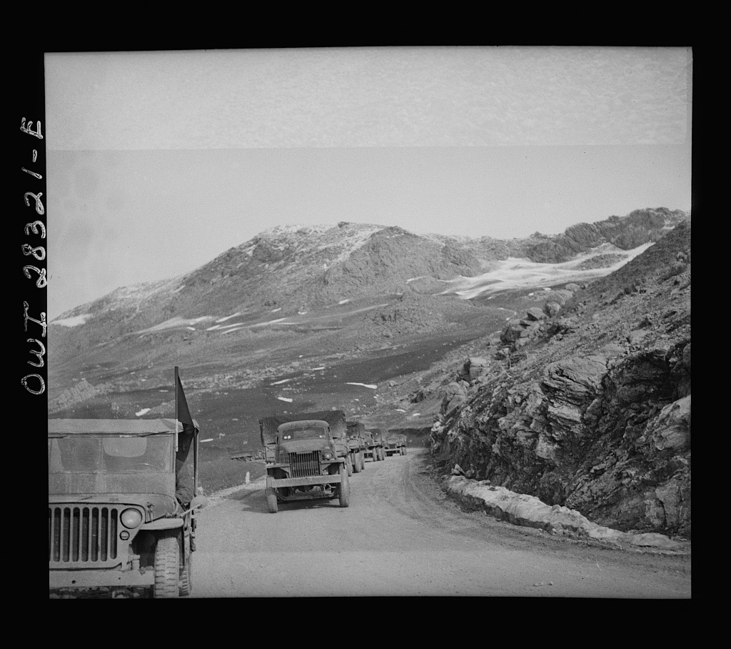 Somewhere in the Persian corridor. A United States Army truck convoy carrying supplies for the aid of Russia. Part of the convoy pulling up a mountain road. The convoy leader in a jeep at the left