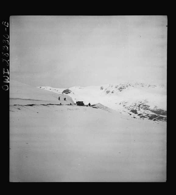 Somewhere in the Persian corridor. A United States Army truck convoy carrying supplies for Russia. Trucks are rounding a mountain peak. Iranian workmen who keep the road open are standing aside as the trucks move through the snow-covered pass