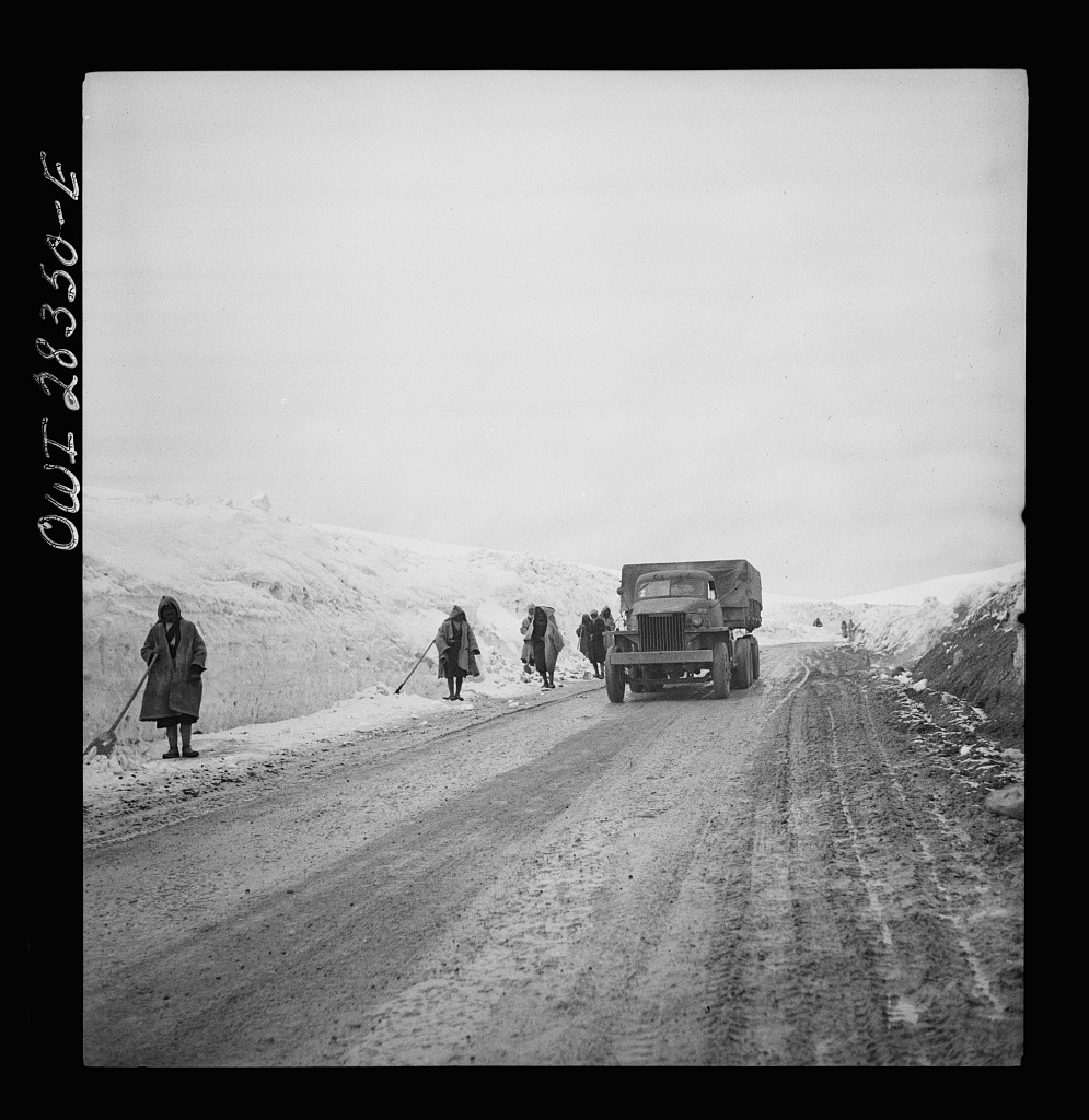 Somewhere in the Persian corridor. A United States Army truck convoy carrying supplies for Russia climbing a snowbound mountain pass being cleared by Iranian road workers who are fighting to keep the road open