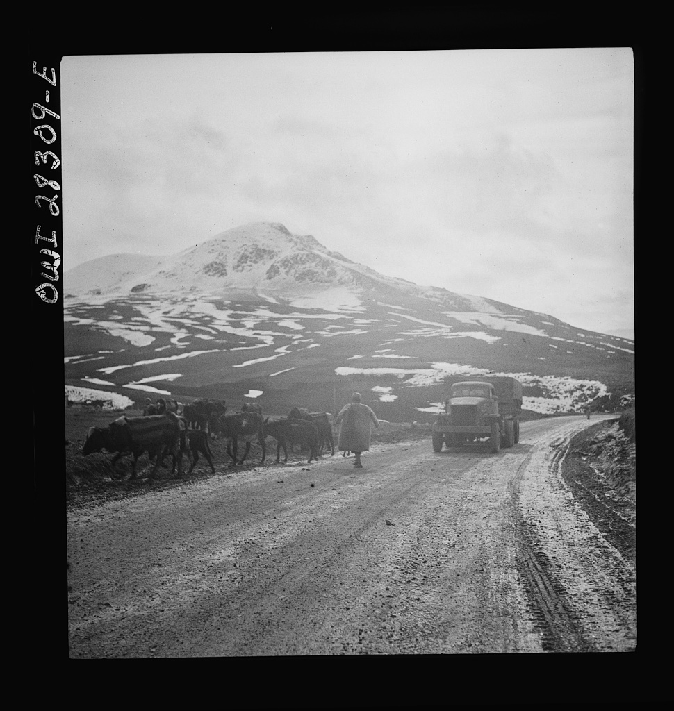 Somewhere in the Persian corridor. A United States Army truck convoy carrying supplies for the aid of Russia. An Iranian native moving his livestock from the mountain road as a United States truck passes
