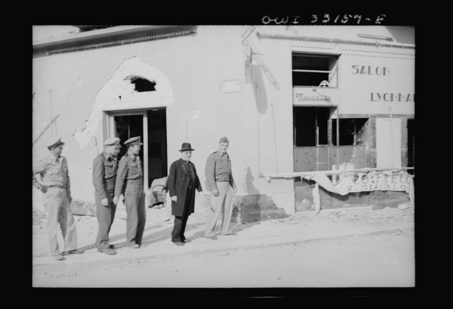 Sousse, Tunisia. Archbiship Spellman of New York and flyers of the US Army 9th airforce, touring the street to inspect bomb damage