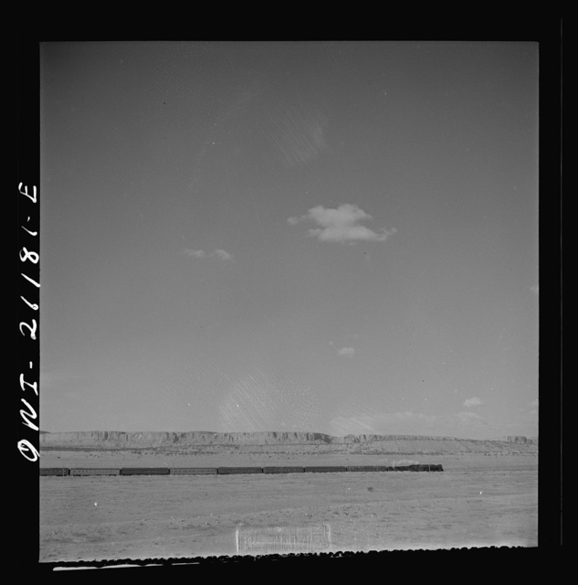 South Chaves (vicinity), New Mexico. On the Atchison, Topeka and Santa Fe Railroad between Belen and Gallup, New Mexico, passing an eastbound passenger train