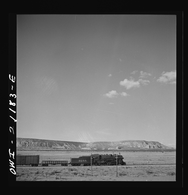 South Chaves (vicinity), New Mexico. On the Atchison, Topeka and Santa Fe Railroad between Belen and Gallup, New Mexico, passing an eastbound freight train