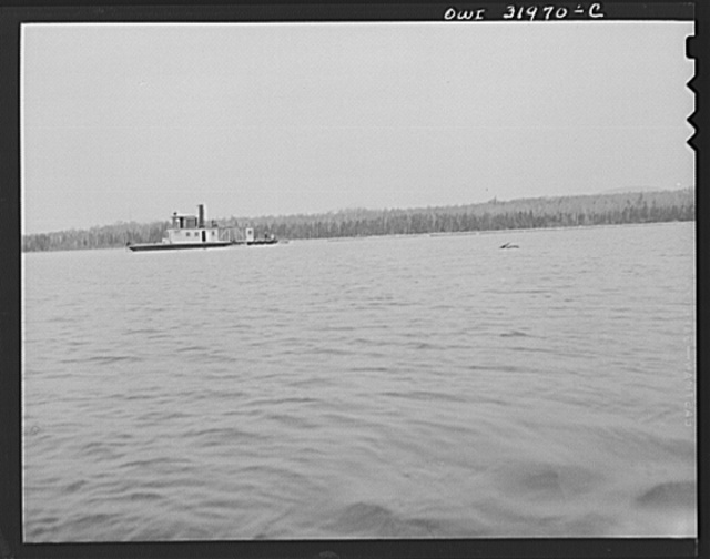 Spring pulpwood drive on the Brown Company timber holdings in Maine. Side-wheel steamer, which tows the pulp wood twelve miles down Mooselookmeguntic Lake, returns with an empty boom which will exchange for a full one