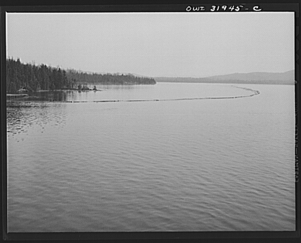 Spring pulpwood drive on the Brown Company timber holdings in Maine. The safety boom, a second boom to provide extra protection when towing the logs, is anchored temporarily while the steamer goes to pick up the full boom it is to tow across Mooselookmeguntic Lake