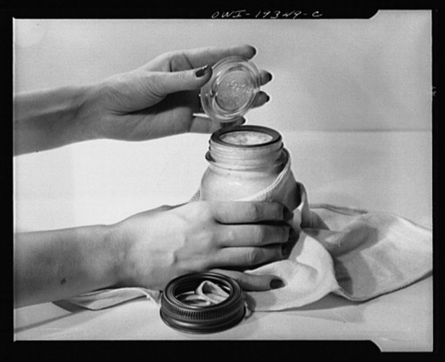 Steel-saving glass-top jars recommended by the War Production Board, Containers Division, for home canning of the Victory garden fruits and vegetables in 1943. First step in sealing a jar is to fit the wet, sterilized rubber ring around the projection on the underside of the glass lid, also sterilized