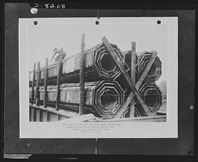 Substitute materials. A shipment of 1,488 feet of 18-inch, 24-inch, 30-inch and 36-inch wooden pipe on one flat car. Weight 70,020 pounds. An equal footage of reinforced concrete pipe weighs 455,412 pounds, requires over ten cars. These pipes, used in place of corrugated iron or reinforced concrete pipes, are made of sections cut from short lengths of wood. Locking of adjacent rings with hardwood dowel pins produces a flexible structure. About 100,000 feet of these wooden pipes were installed in 1942 in drainage culverts, storm sewers and conduits, under highways and at army camps, naval stations, airfields and ordnance plants