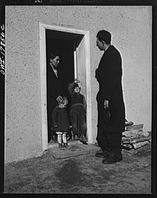 Taos County, New Mexico. Father Cassidy, the Catholic priest of the parish of Penasco, visiting Juan Lopez, a parishioner in Trampas