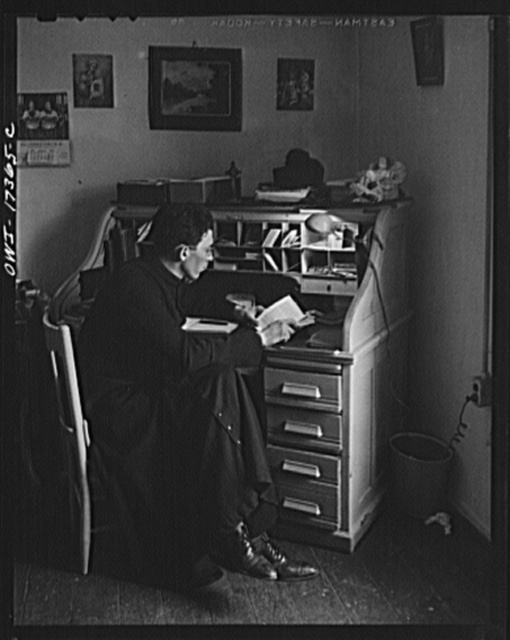 Taos County, New Mexico. Father Cassidy, the Catholic priest of the parish of Penasco, at his desk