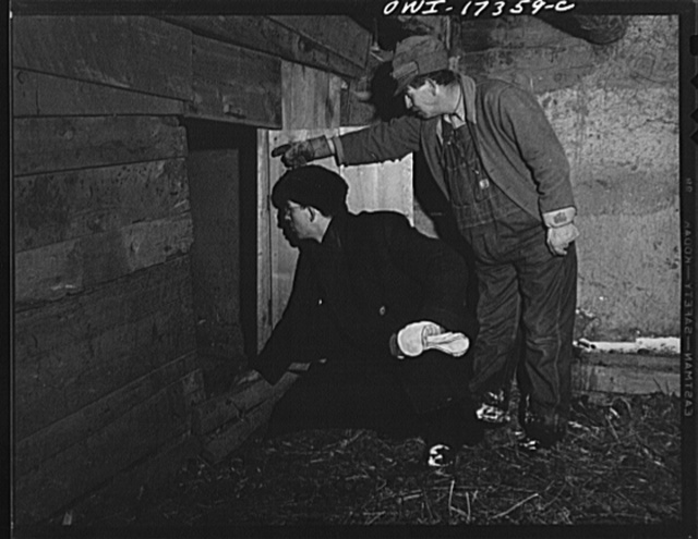 Taos County, New Mexico. Father Cassidy, the Catholic priest of the parish of Penasco, inspecting a parishioner's property so he may be able to advice him