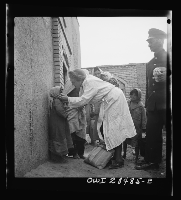 Teheran, Iran. Mrs. Louis Dreyfus, wife of the United States Minister to Iran, distributing food and medical supplies in the poorer section of the city