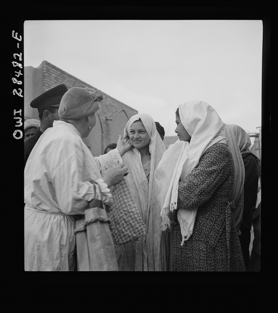 Teheran, Iran. Mrs. Louis Dreyfus, wife of the United States Minister to Iran, talking with native girls