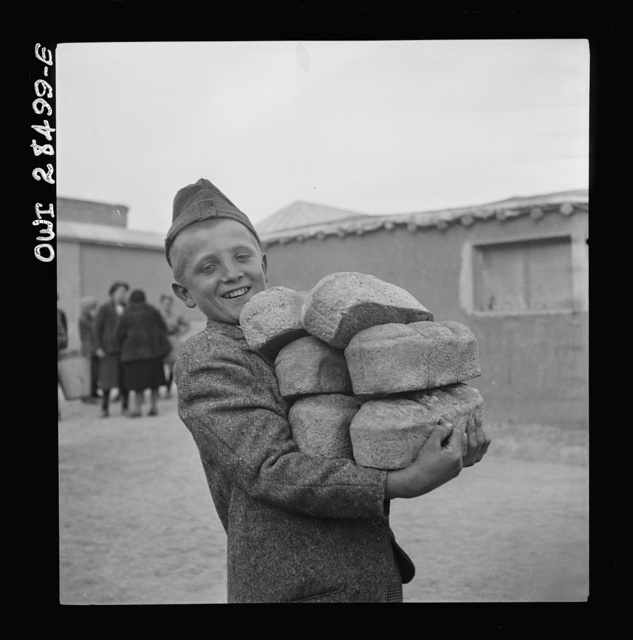 Teheran, Iran. Polish youngster carrying an armload of loaves of bread made from Red Cross flour at an evacuation camp