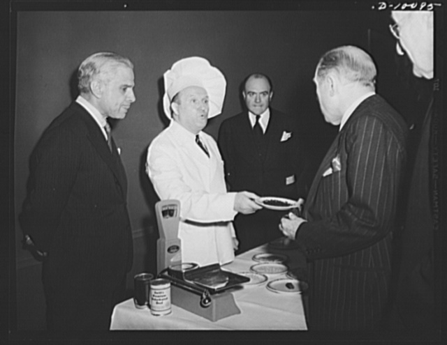 The Ambassador of Greece, Cimon P. Diamantopoulos watches as Representative Sol Bloom, chairman of the House Committee on Foreign Affairs accepts a plate of food, which had first been dehydrated, then rehydrated, at a luncheon held in observance of the second anniversary of lend-lease, on March 11, 1943, at the Hotel Statler, Washington, D.C.