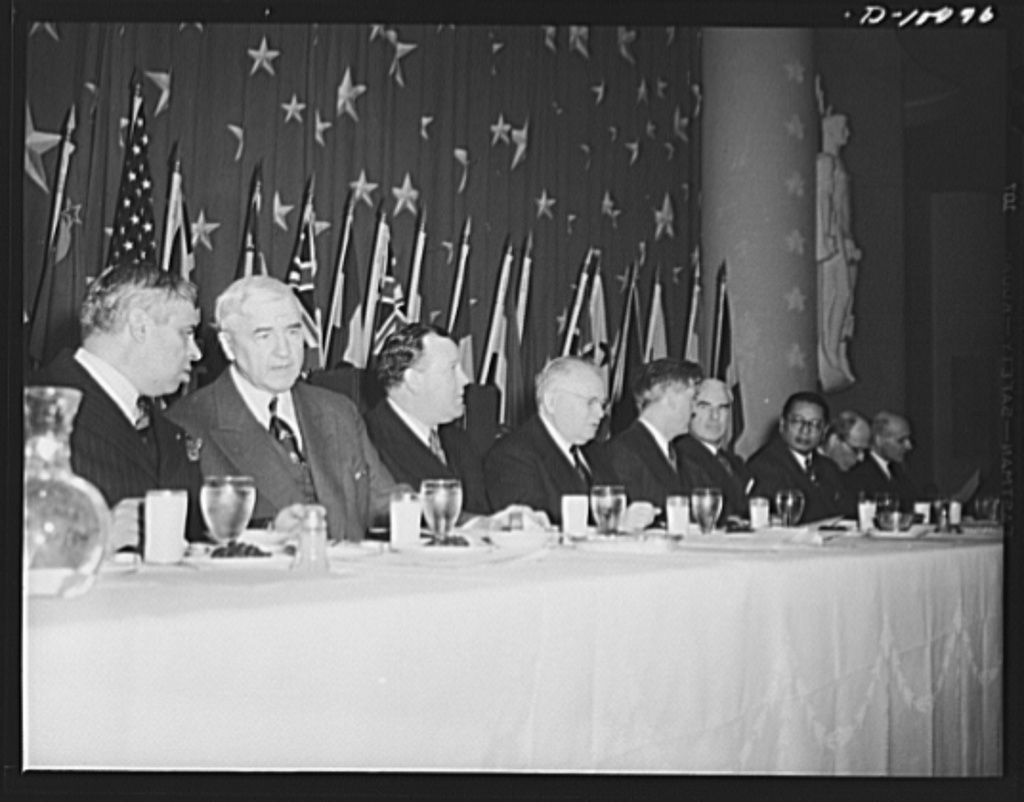 The Mexican Ambassador Senor Dr. Don Francisco Castillo Najera; Secretary of Commerce Jesse Jones; Norwegian foreign minister Trygze Lie; Russian ambassador Maxim Litvinov; Vice-President Henry A. Wallace; lend-lease administrator Edward R. Stettinius, Jr.; Chinese foreign minister T.V. Soong; British ambassador Lord Halifax; and the Belgium ambassador Count Robert van der Straten-Ponthoz, on the dais at luncheon held in observance of the second anniversary of lend-lease, on March 11, 1943, at the Hotel Statler, Washington, D.C.