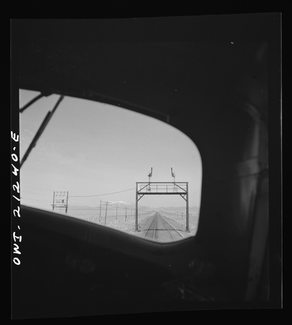 The San Francisco peaks, in the Sierra Nevada range near the California border, seen through the engineer's window of a diesel freight locomotive on the Atchison, Topeka and Santa Fe Railroad between Winslow and Seligman, Arizona