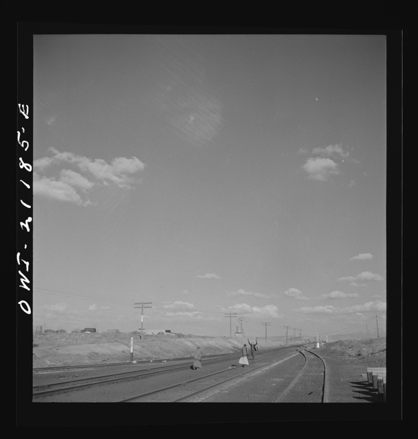 Thoreau, New Mexico. Indian woman crossing the tracks as the conductor gives the highball along the Atchison, Topeka and Santa Fe Railroad between Belen and Gallup, New Mexico