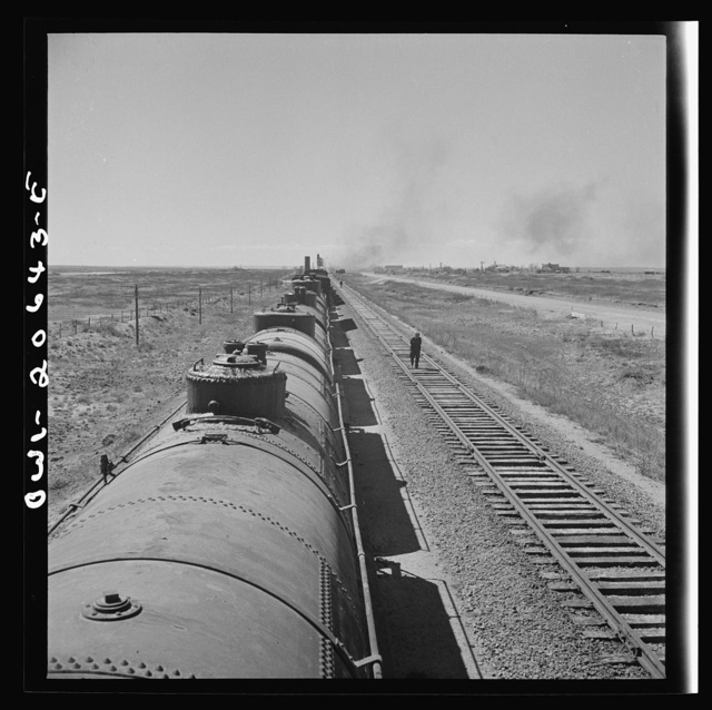 Tolar, New Mexico. Atchison, Topeka, and Santa Fe Railroad train between Clovis and Vaughn, New Mexico stopping for water. A brakeman walking the length of the train for inspection