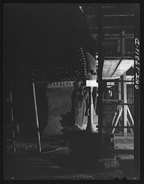 Topeka, Kansas. Welder at work on part of a fire box of a locomotive in the Atchison, Topeka and Santa Fe Railroad locomotive shops