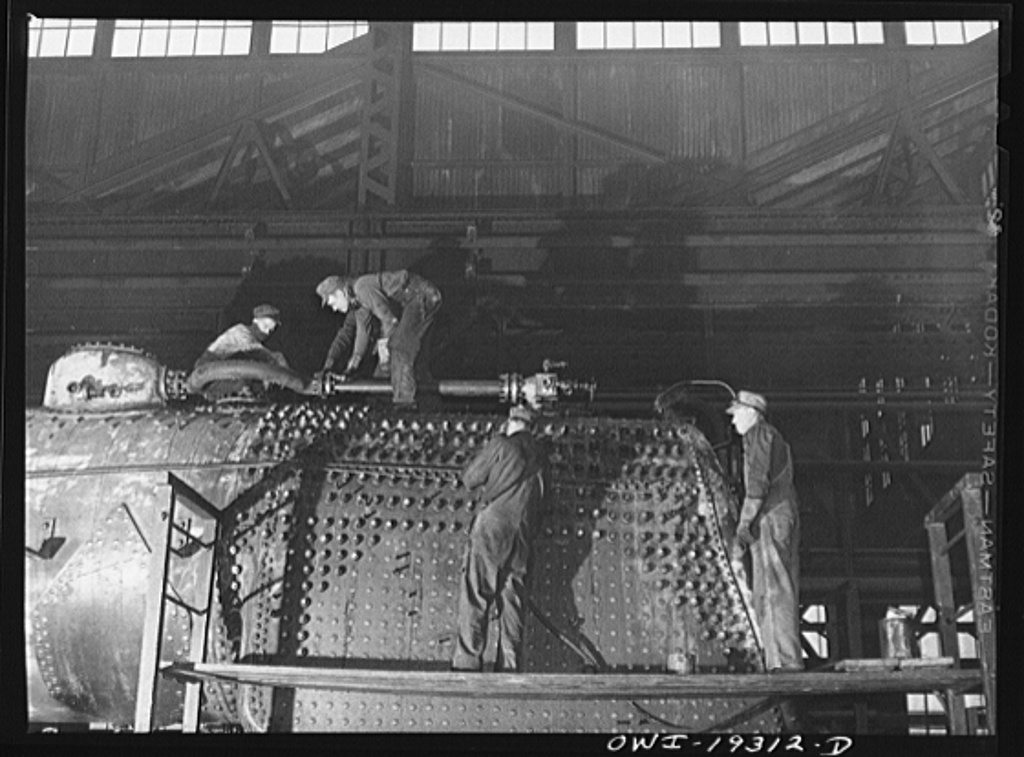 Topeka, Kansas. Working on the fire box end of an engine in the Atchison, Topeka and Santa Fe Railroad locomotive shop