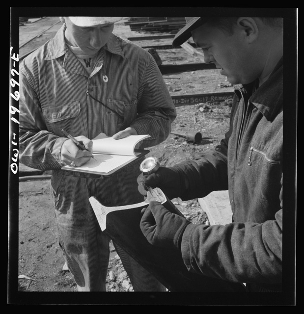 Topeka, Kansas. Workmen of the test department of the Atchison, Topeka, and Santa Fe Railroad shops examining the extent of the fissure on a rail first detected as faulty by the rail detector car