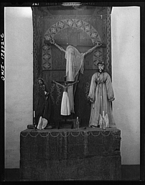 Trampas, New Mexico. Altar in the left of a transept in a church which was built in 1700 and is the best-preserved colonial mission in the Southwest, is painted in tones of grey and blue. A Coca-Cola bottle is holding a candle on the altar