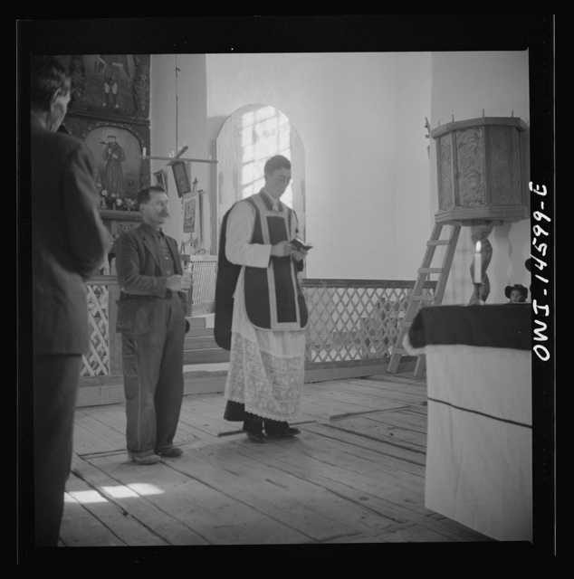 Trampas, New Mexico. Father Cassidy, and the Archelite of the church officiating at a memorial mass in a church which was built in 1700 and is the best-preserved colonial mission in the Southwest