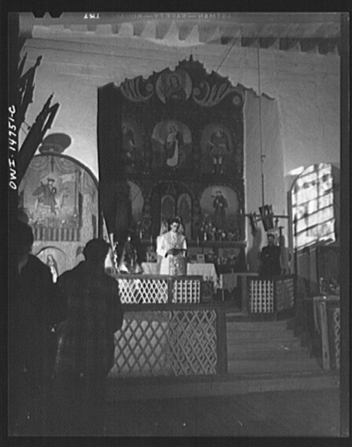 Trampas, New Mexico. Father Cassidy, resident priest of the parish of Penasco, giving a sermon in Spanish. The acolyte of the church is standing at his left