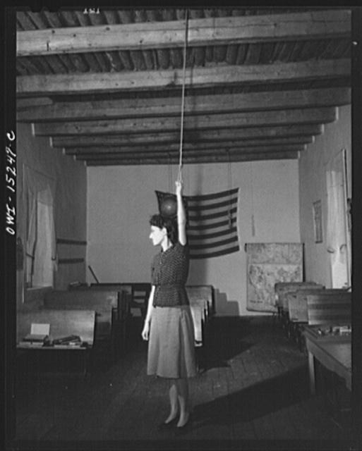Trampas, New Mexico. Grade school teacher ringing a bell to call her class