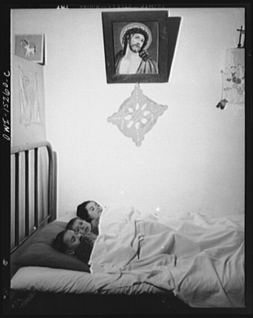Trampas, New Mexico. In many Spanish-American homes, mattresses are rolled out on the floor at night. But by putting three under a blanket the Lopez family all sleep in beds