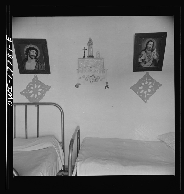 Trampas, New Mexico. In the home of Juan Lopez, the majordomo (mayor). Years ago ancient hand-carved and painted santos hung on the walls in place of these cheap religious prints. Collectors have bought up almost all native art
